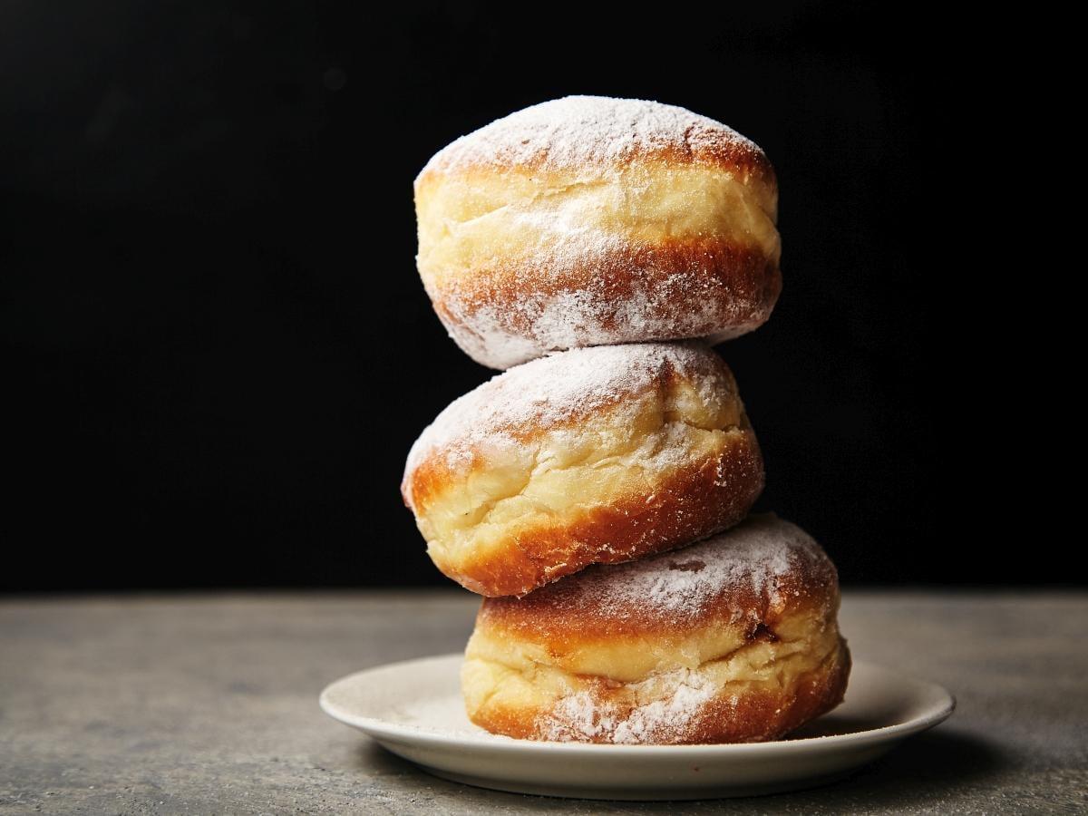 Na zdjęciu znajdują się trzy pączki z cukrem pudrem.