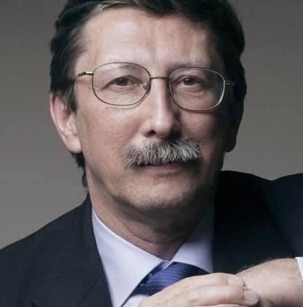 Na zdjęciu jest prof. Jan Żaryn ze splecionymi dłońmi na tle białej ściany