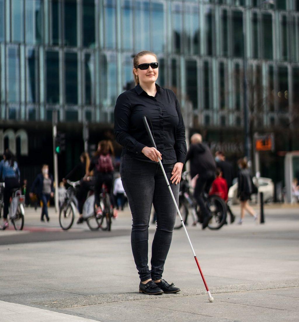 Niewidoma kobieta stoi z białą laską na tle miasta