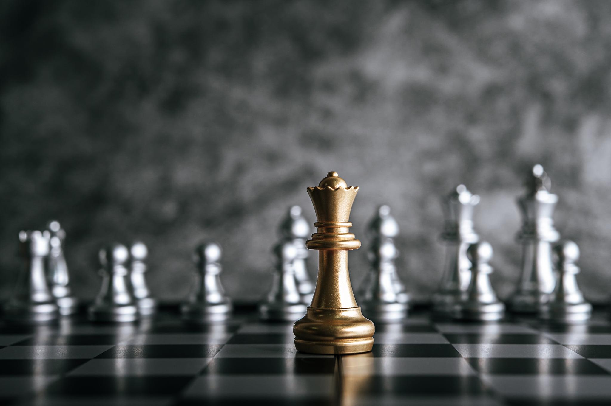 Zdjęcie przedstawia znajdującą się na szachownicy pozłacaną figurę szachową na tle figur srebrnych