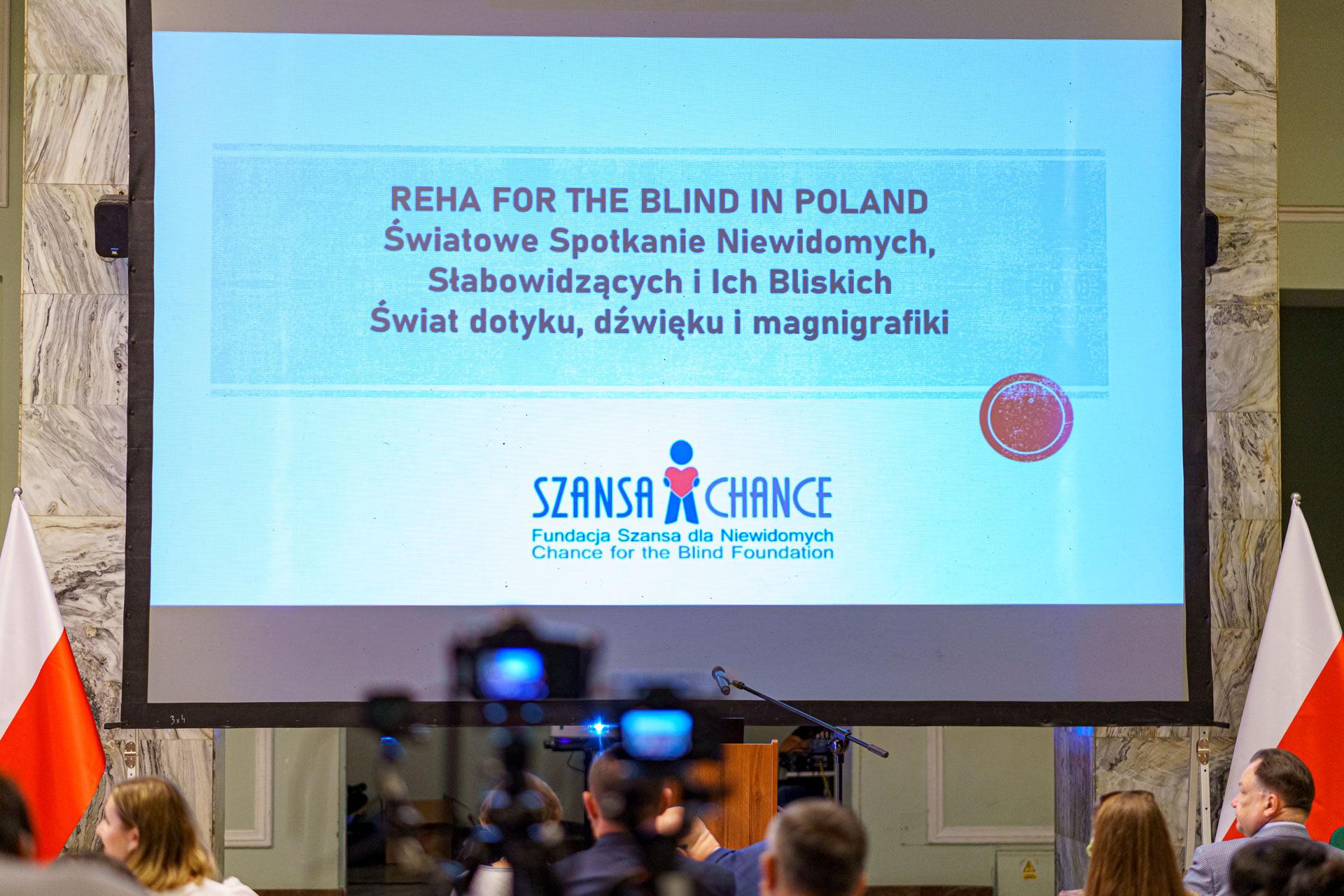 Zdjęcie prezentuje telebim z zeszłorocznej konferencji REHA