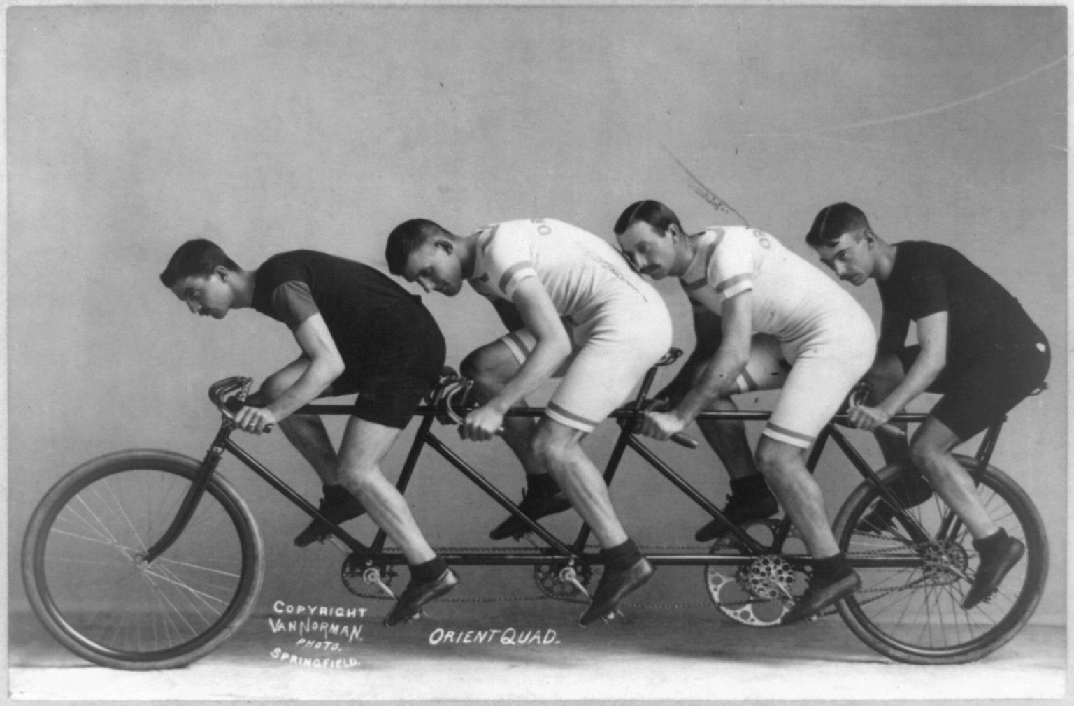 Na zdjęciu znajduje się czterech rowerzystów, na czteroosobowym rowerze.